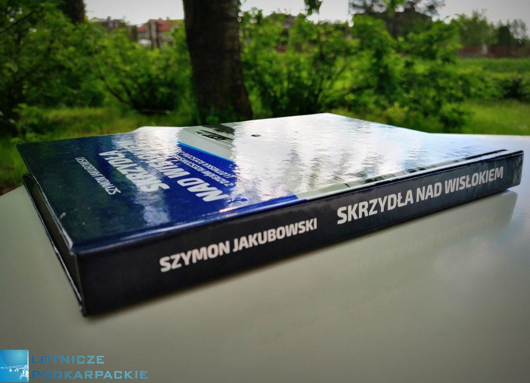 książka leży na białym stole w zielonym sadzie