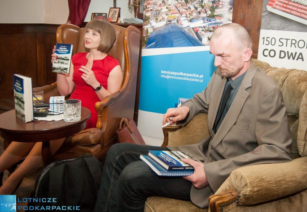kobieta siedząca na fotelu prezentuje książkę, mężczyzna siedzi obok