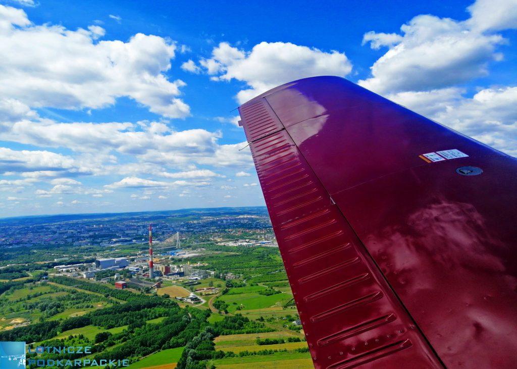skrzydło samolotu, niebo, na dole pola, łaki i domy, krajobraz widziany z lotu ptaka