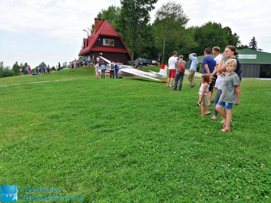 ludzie stoją na zielonej trawie, w tle stoi szybowiec, widać domek