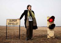 kobieta stoi na zewnątrz obok sygnalizator świetlny i tabliczka z napisem