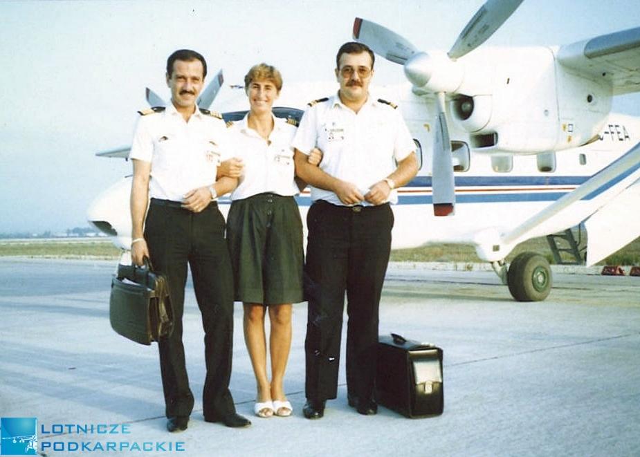 kobieta i dwaj mężczyźni stroją na tle samolotu