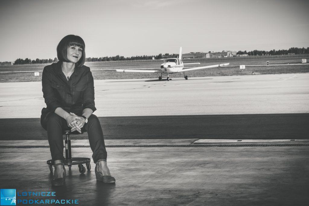 kobieta siedzi na stołku w hangarze w tle jest samolot