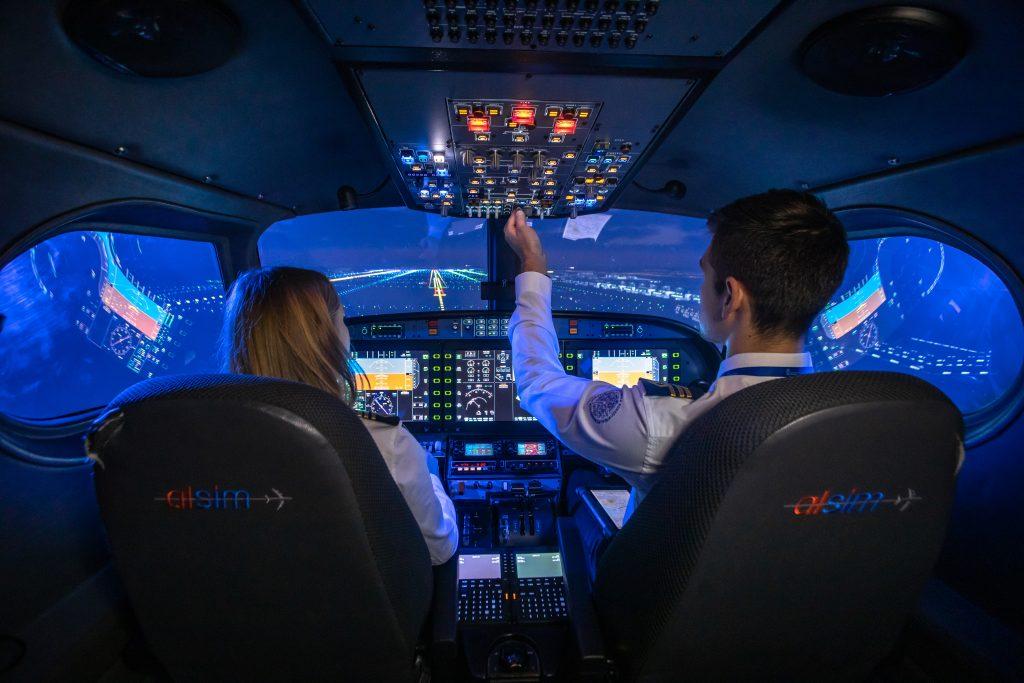 kobieta i mężczyzna siedzą w kokpicie symulatora lotów