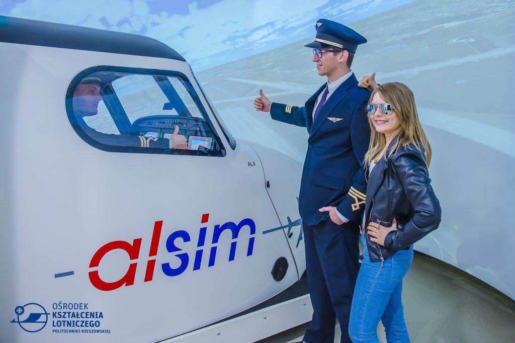 dziewczyna i chłopak stoją, obok kabina symulatora lotu