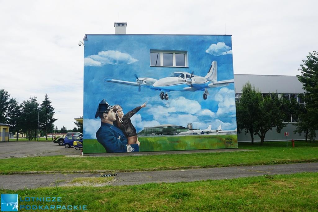 ściana budynku z malowanym pilotem samolotem