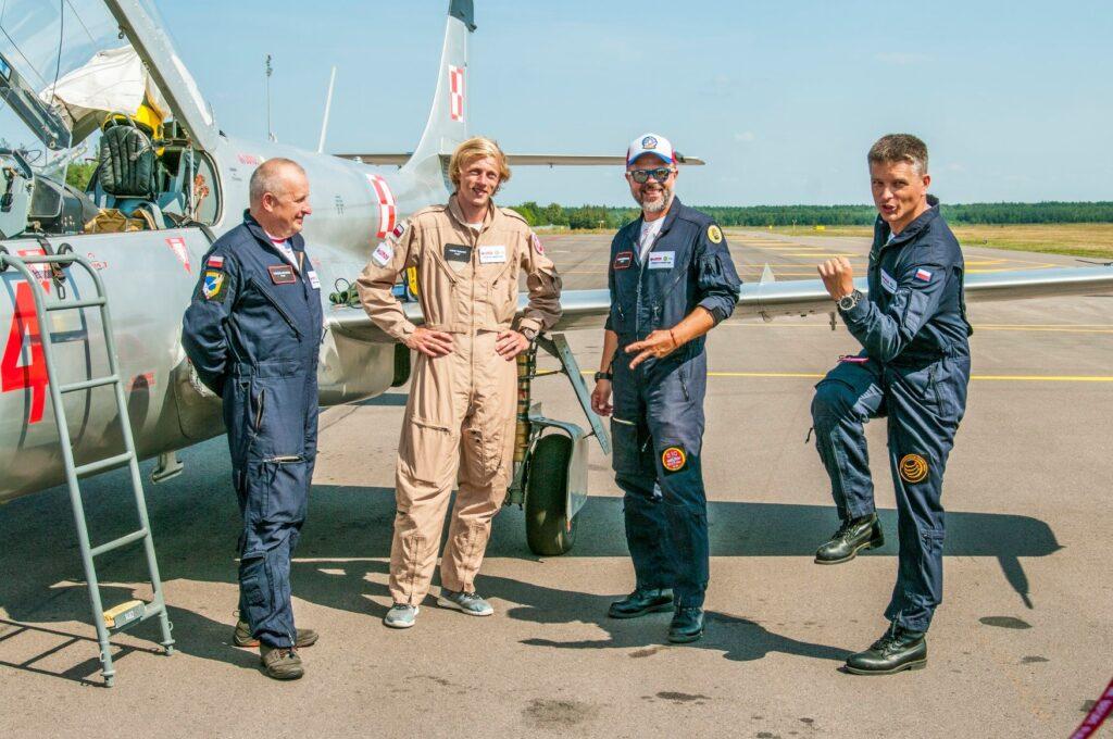 mężczyźni w kombinezonach stoją na tle samolotu