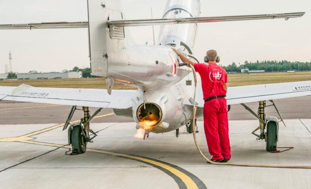 mężczyzna w czerwonym kombinezonie tankuje samolot