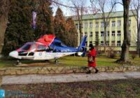 śmigłowiec stroi na tle budynku, obok idzie kobieta w czerwonym płaszczu